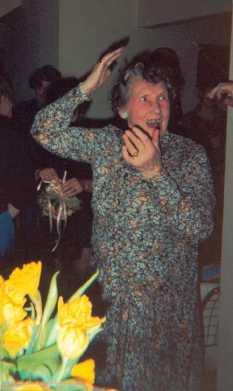"""Ingrid Knudsen ved sønnesønnen <a href=""""?id=41"""">Eriks</a> bryllup 21.3.2001         på Frederiksberg.<br />         Da bruden kastede brudebuketten ud, blev Ingrid den heldige modtager.<br />         Hun stod i denne stilling selv efter, at præstens kone Pia (i baggrunden)       havde lettet Ingrid for buketten."""